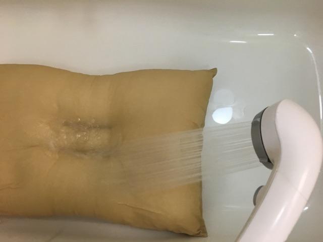 枕にシャワーをかけている
