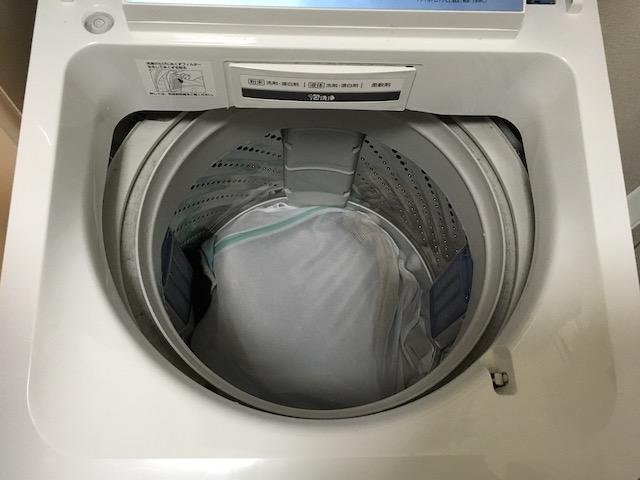 洗濯機の中へセーターを入れる